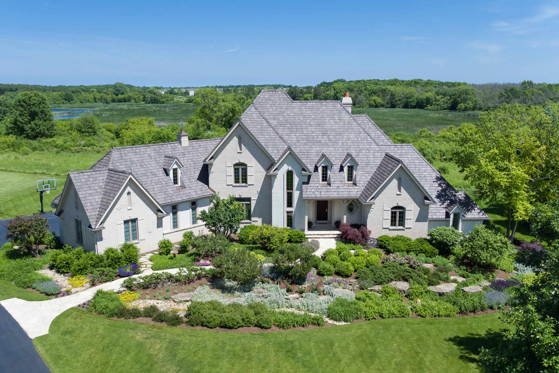Aerial photo of large home with beautiful landscaping in the front.