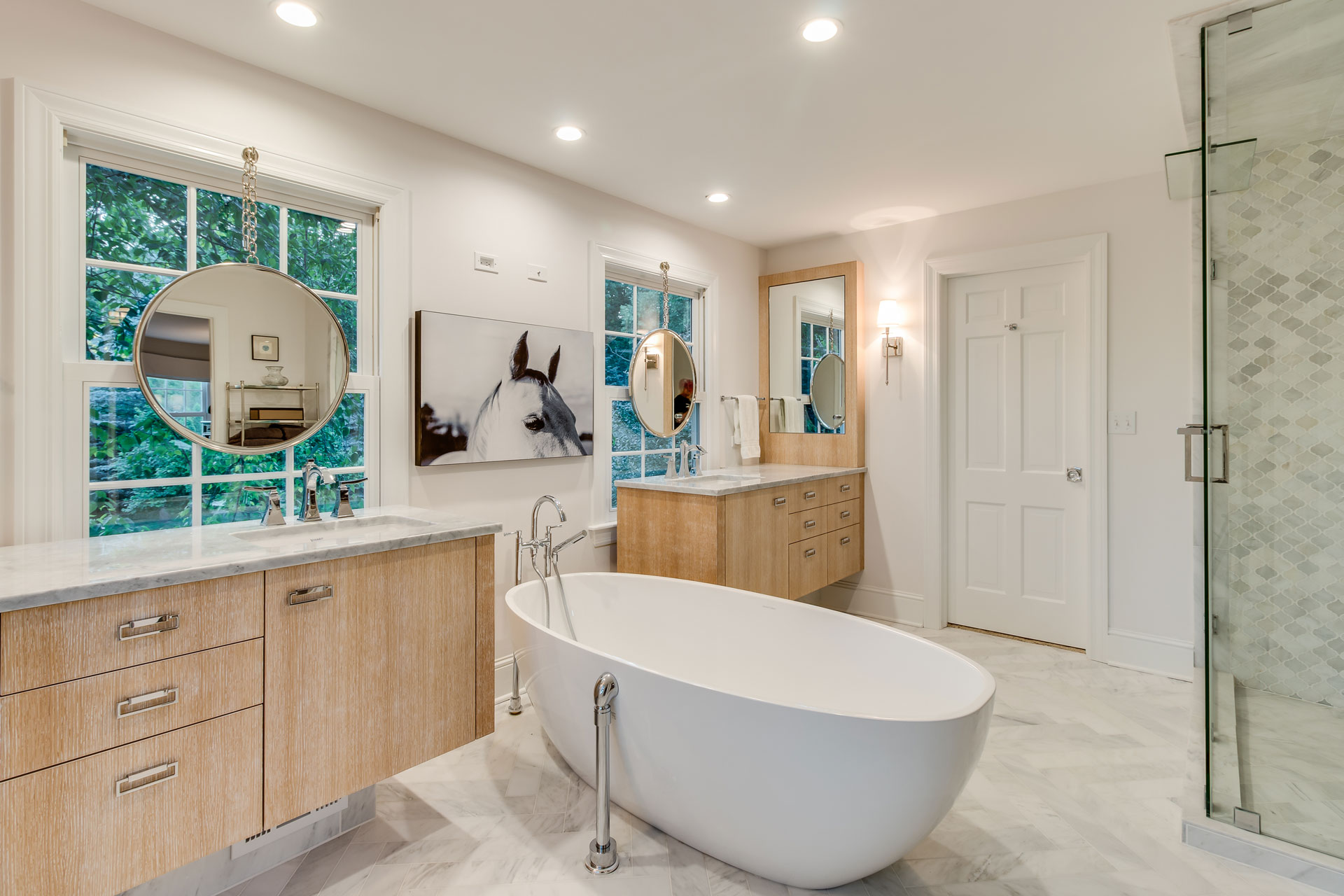 Refinished bathroom with large white tub in center, with symmetrical counter and cabinets on each side. Glass shower enclosure and gray and white tiles.