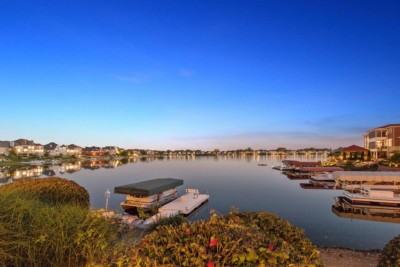 Sunset photo of lake surrounded by large homes.